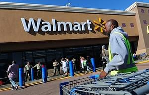 A Walmart employee gathers pushcarts as police...