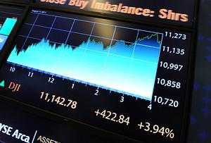 An electronic display shows Dow Jones Industri...