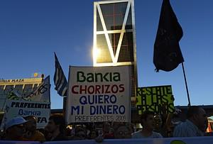 People holds a placard reading 'Bankia thieves...