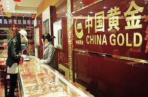 A Chinese woman buys gold jewellery at a gold ...