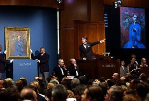Tobias Meyer (C) of Sotheby's points to bidder...