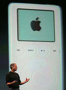 Apple CEO Steve Jobs speaks in front of a pict...