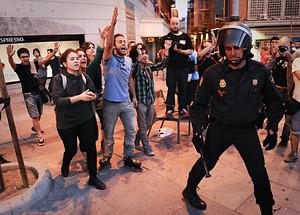 Protesters shout at a policeman as they take p...