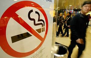 A man walks past a no smoking sign in a shoppi...