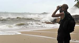 A man takes a photograph of rough seas caused ...