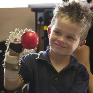 "Liam enjoys his ""bionic hand"", the product of a 3D Printer (Image courtesy of MakerBot)"