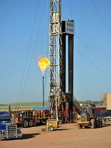 Natural gas is burned off next to an oil well ...