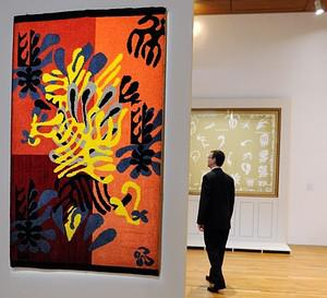 A man looks at gouache painted papers cut by F...