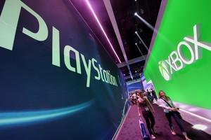 Attendees walk between signs for Sony PlayStat...
