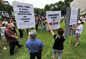 Protesters display placards during a May Day p...