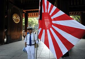 A worshipper stands with a Rising Sun flag whi...