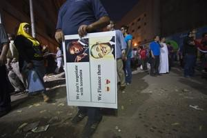 An Egyptian man holds an image of US President...