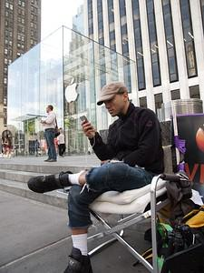 A man waits in line outside the Apple store on...