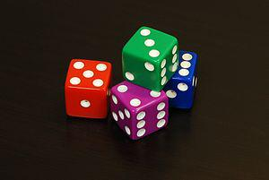 English: Four coloured 6 sided dice arranged i...