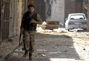 A rebel runs for cover during heavy clashes wi...