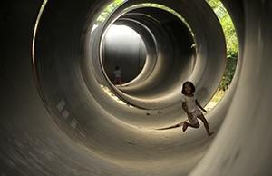 Children play inside steel pipes that will be ...