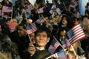 New citizens wave US flags before being sworn ...