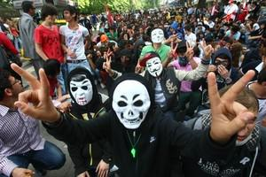 Anti-government protesters wearing masks and h...