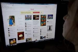 A woman looks at the internet site Pinterest.c...