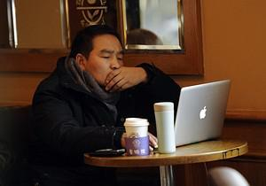 A man uses his computer in a coffee shop in Sh...