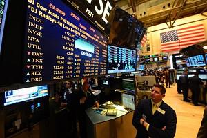 A trader looks at an electronic board indicati...