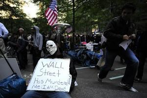 Occupy Wall Street participants carry on their...