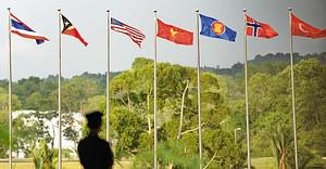 A Brunei policeman stands in front of flags fr...