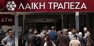 People queue up outside a Laiki bank branch in...
