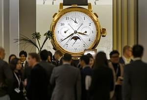 People gather near a giant model watch by watc...