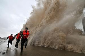 A huge wave hits the dike as guards run along ...