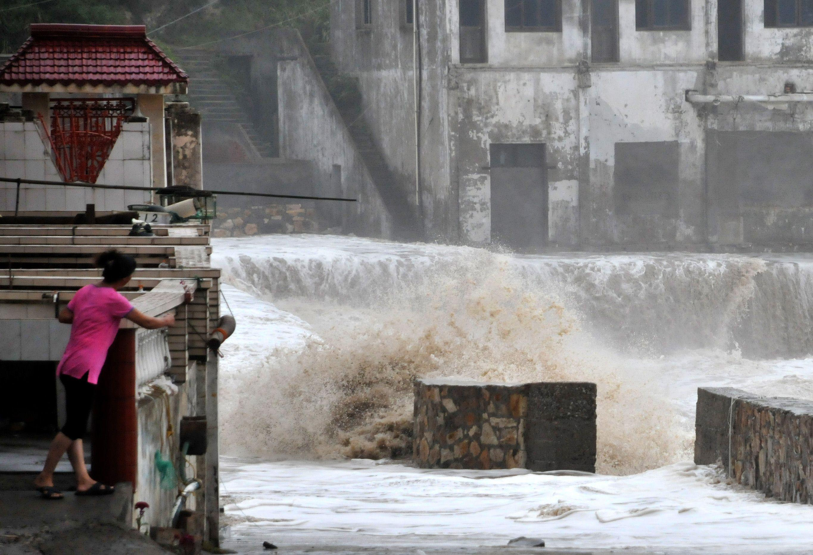 A woman looks on as a huge wave hits the dike as Typhoon Fitow moves to make its landfall in Wenling, east China's Zhejiang province on October 6, 2013. China was on its highest alert for Typhoon Fitow on October 6, with tens of thousands evacuated as the storm was set to slam into the east coast. AFP PHOTO