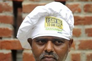 A Indian chef wearing, wearing a hat against g...