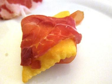 Gnoccho fritto is a warm fried dough puff wrapped in prosciutto di Parma, at Italy's Ai Due Platani.