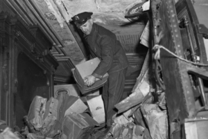 A police officer attempts to clear a path through the Collyer mansion, where two reclusive brothers died as a result of their hoarding.