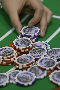 A croupier poses with gaming chips at a gaming...