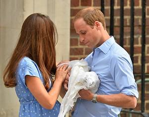 Prince William (R) takes the baby from Catheri...