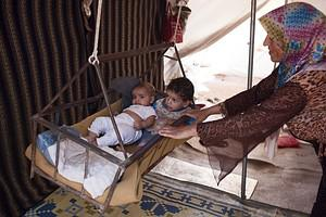 A Syrian refugee woman rocks her children in a...