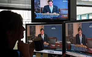A journalist watches C-SPAN  TV on computer sc...