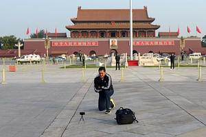 A man takes a photo at Tiananmen square in Bei...