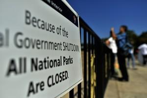 A shutdown sign is seen as tourists take pictu...