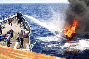 Sailors on USS Rentz (FFG 46) combat a fire se...