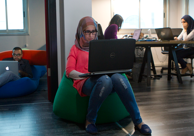 Palestinian Web designer Walaa Abu-Lebdeh, 24, working on her computer at Yamsafer. Also seen in the... [+] background is Rana Hamarsheh (right), 26, a web designer, and computer engineer Sarah Fazaa, 22, a business administrator. Amer Amin, 23, a UX D and user expert is seen working on a Macintosh computer laptop.