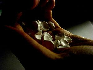 English: a hand holding unidentified white pills