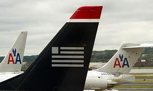 A US Airways tail rest on the tarmac near two ...