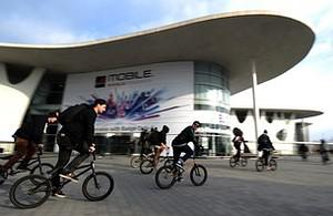 A group of cyclists ride past the Mobile World...