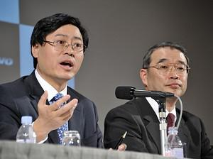 Lenovo CEO Yang Yuanqing (L) speaks next to NE...