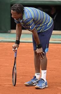 France's Gael Monfils  holds his knee in pain ...