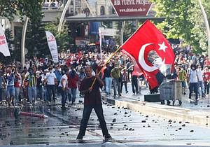 A protestor holds a Turkish flag with a portra...