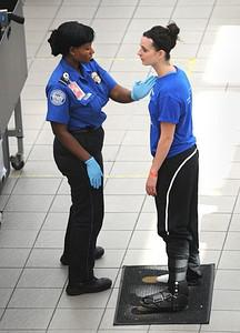 A passenger (R) is patted down by a Transporta...