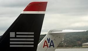 A US Airways tail rest on the tarmac near an A...